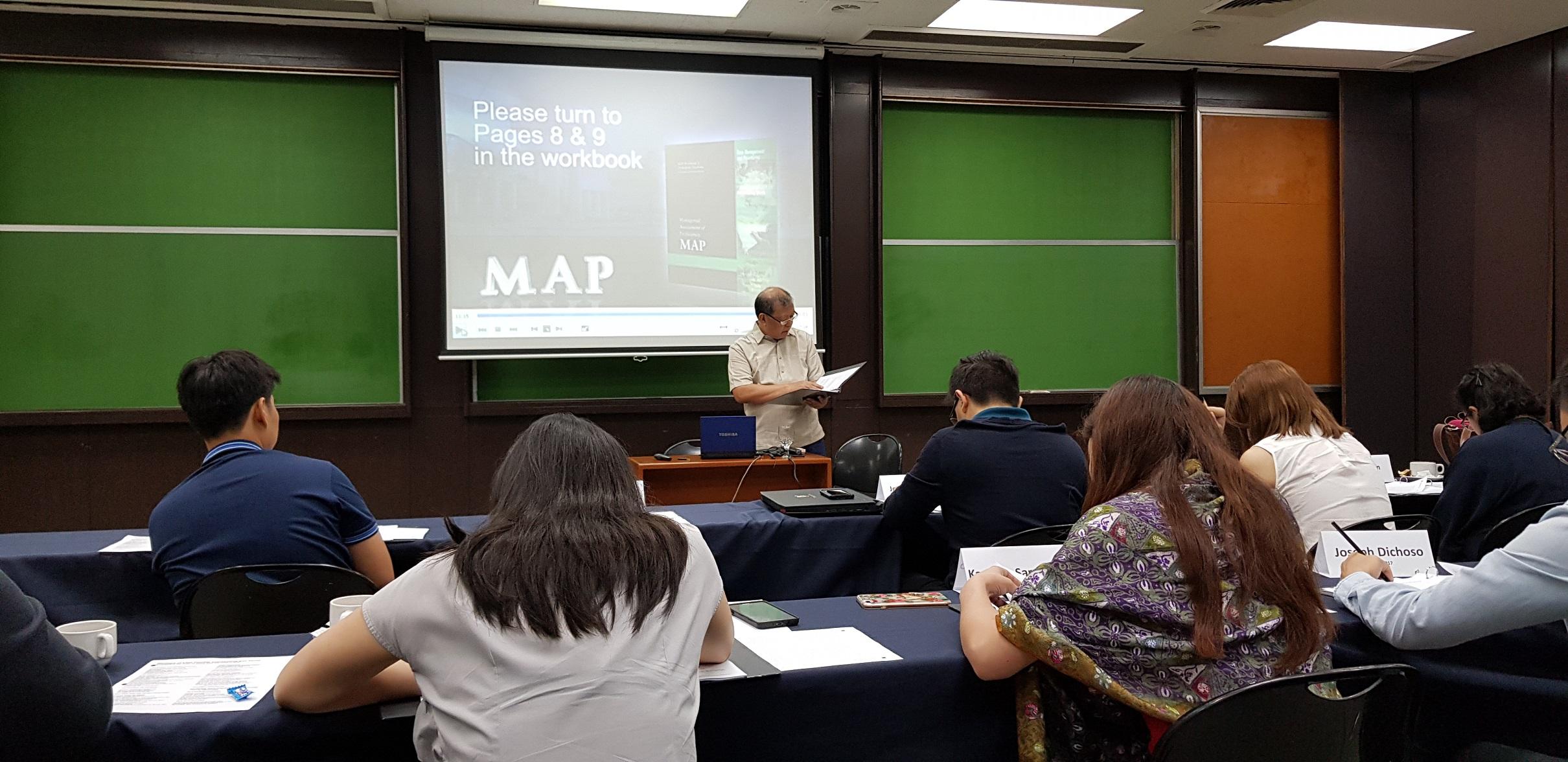 MDP alumnus Galo Ignacio speaks in front of recent AIM graduates during Day 1 of the MAP session.